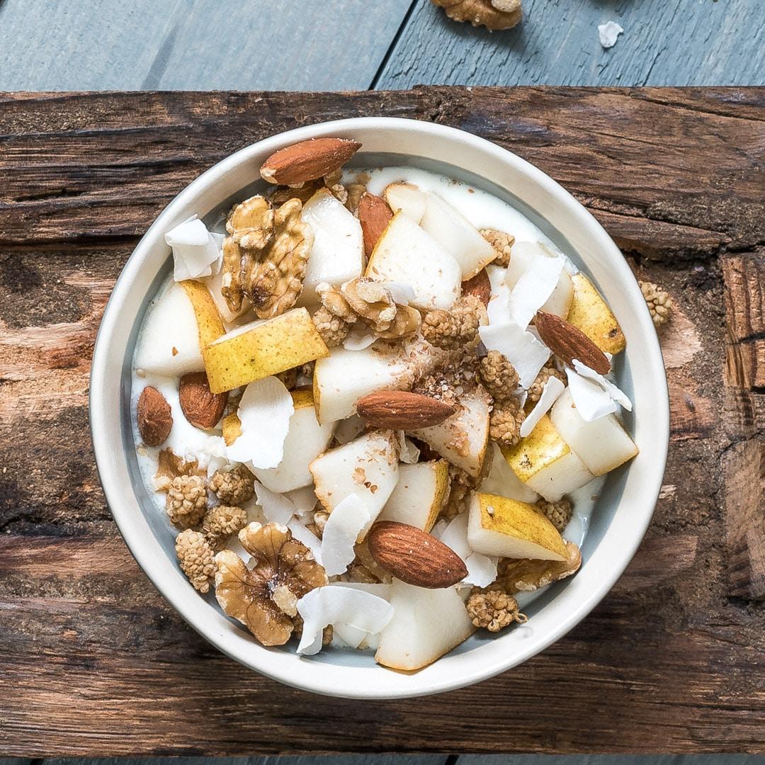 Yoghurt met peer, amandelen, walnoten, moerbeien en kokosvlokken