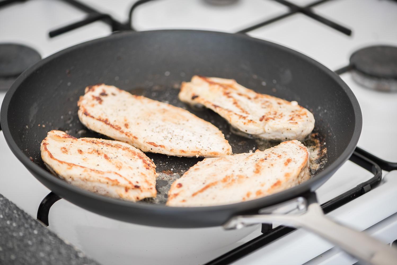 Foto van kipfilet die wordt gebraden in een pan