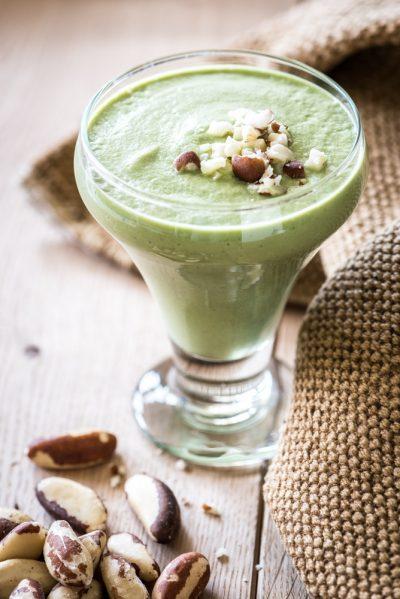 Afbeelding van een smoothie in een glas met stukjes paranoot bovenop