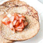 Afbeelding van ontbijt pannenkoeken geserveerd met aardbeien en kokosrasp