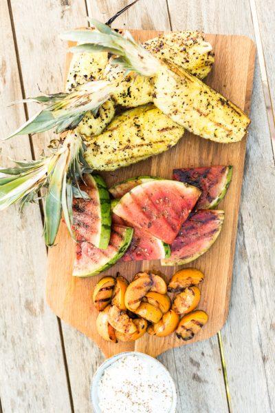 Plank met ananas, watermeloen en kaki gegrild van de barbecue