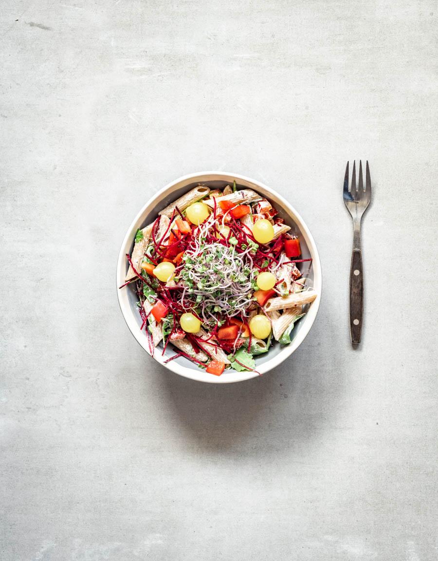 salade van volkoren penne met rucola, zure room en zilveruitjes